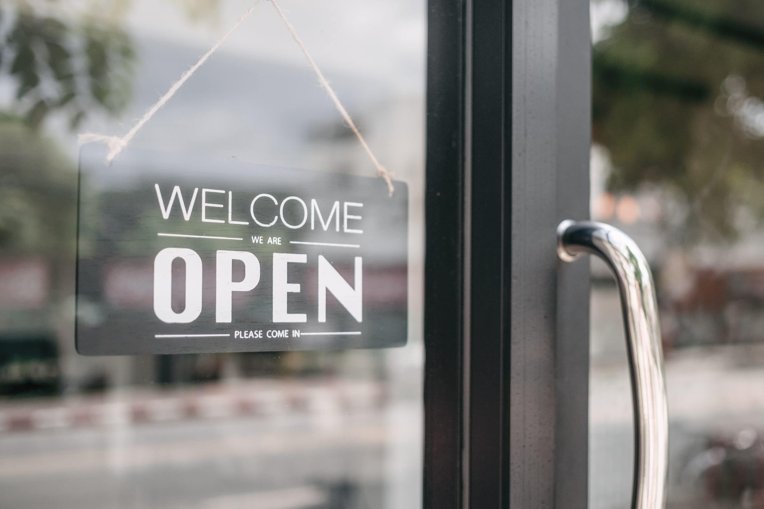 Closeup of open and welcome to store sign board at the door.